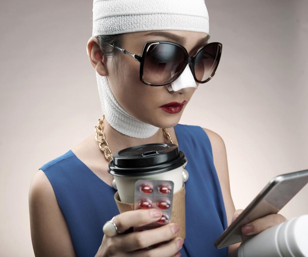 Burun estetiği ameliyatı olmuş, bir elinde haplarını ve kahvesini tutarken diğer elinde tuttuğu cep telefonundan mesajlarını okuyan uzak doğulu bir kadın