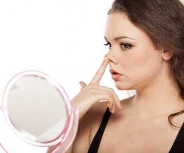 Aynada burnunu inceleyen bir kadın fotğrafı